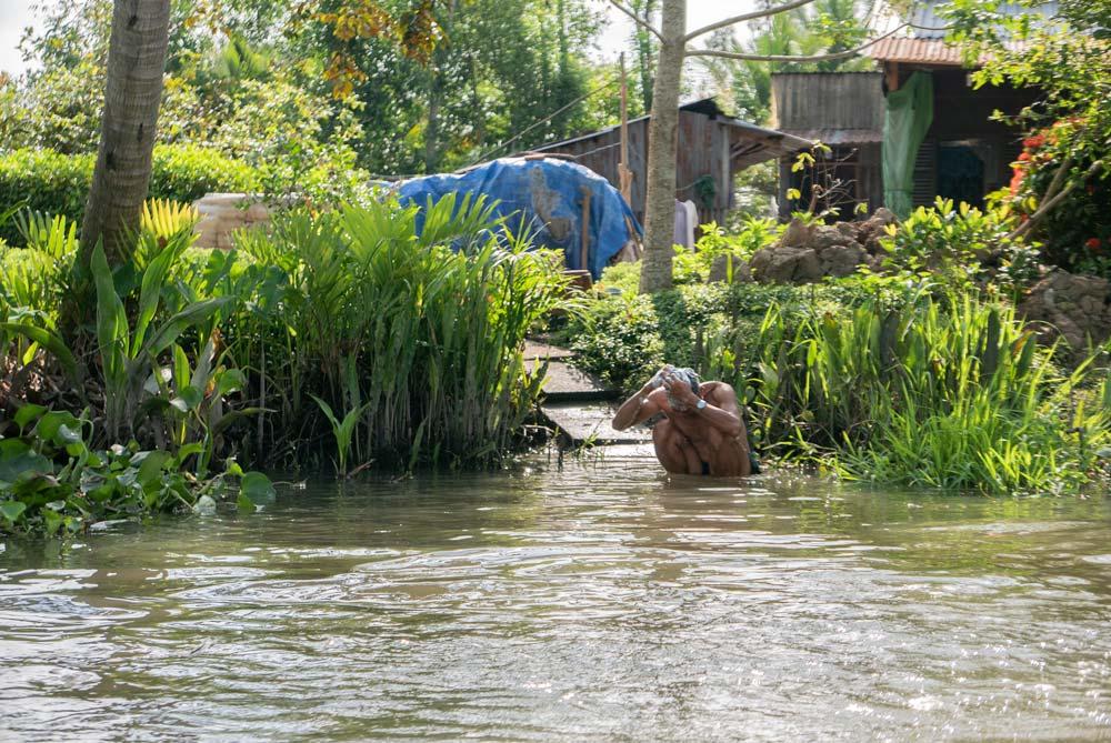Un señor se baña y se lava la cabeza con jabón en las orillas del Río Mekong. Al lado su casa, flores y árboles. Te espero en la Conchinchina