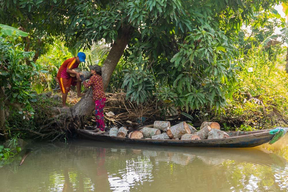 Vida en el Río Mekong. Dos persona cargan troncos de leña en una barca. Te espero en la Conchinchina