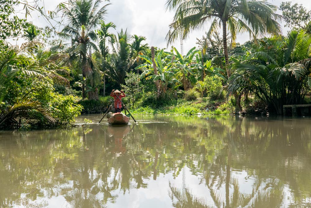 Un barquero rema con su gorro típico vietnamita en el Río Mekong rodeado de una verde y frondosa vegetación. Te espero en la Conchinchina