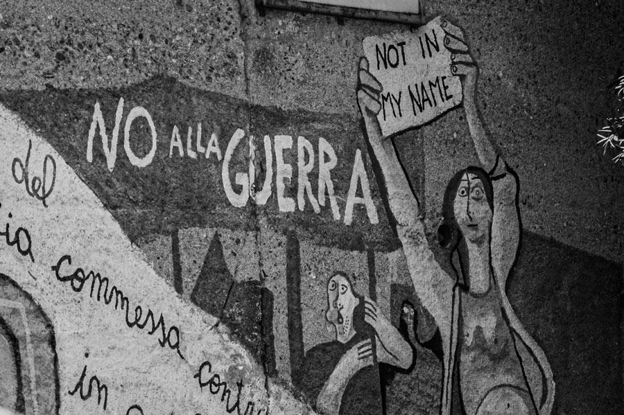 """Pintura mural donde vemos una chica que eleva un cartel que pone """"No en mi nombre"""". Se trata de una pintura que reivindica el No a la Guerra. Orgosolo. Cerdeña."""