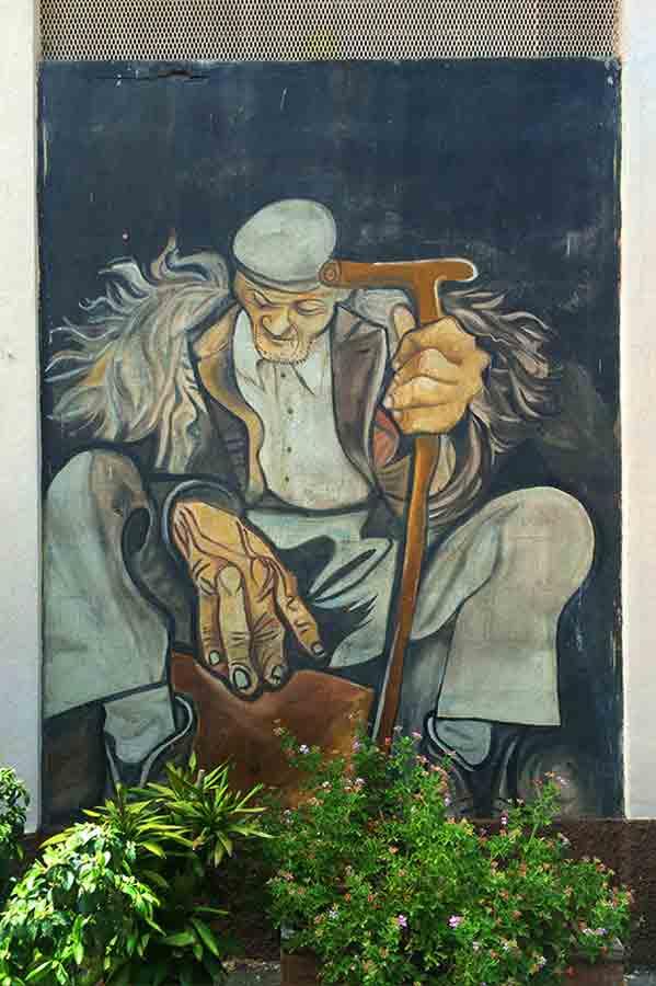 Pintura mural donde vemos un señor mayor con un bastón. Orgosolo. Cerdeña.