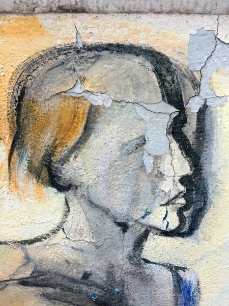 Pintura mural de una cara muy desgastada por el tiempo. Orgosolo. Cerdeña.