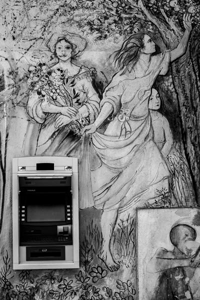 Pintura mural de unas ninfas rodeando un cajero automático del banco. Orgosolo. Cerdeña.