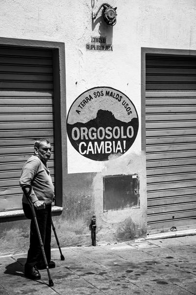 Fotografía de un señor del pueblo con un cartel al fondo que pone A Terra dos malos usos, Orgoslo, cambia! Orgosolo. Cerdeña