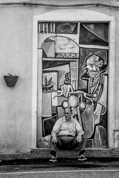 Señor sentado en una pared con murales. Blanco y negro. Orgosolo. Cerdeña