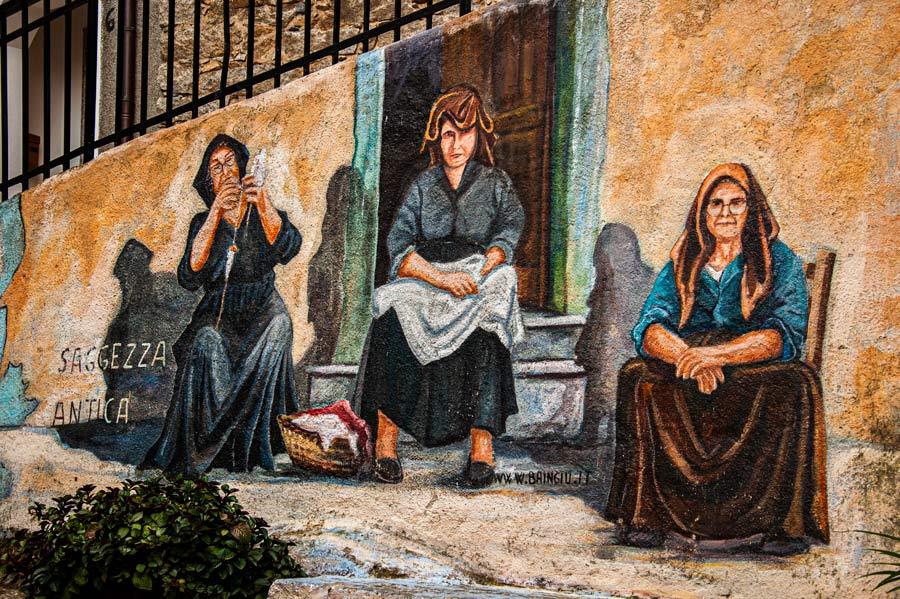 3 costureras en la puerta de una casa. Pintura mural. Orgosolo. Cerdeña.