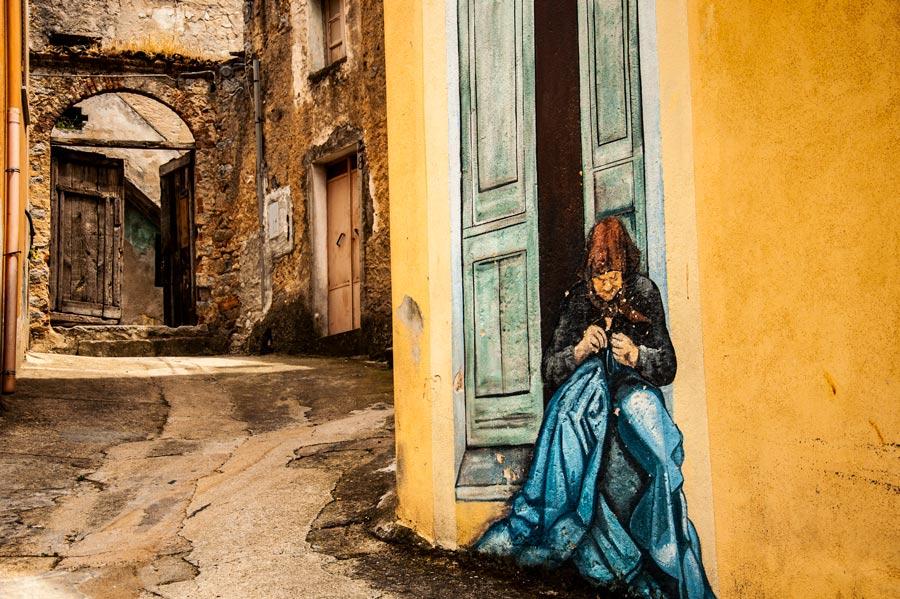 Preciosa calle donde vemos una pintural mural con una señora cosiendo en la puerta de su casa. Orgosolo. Cerdeña.