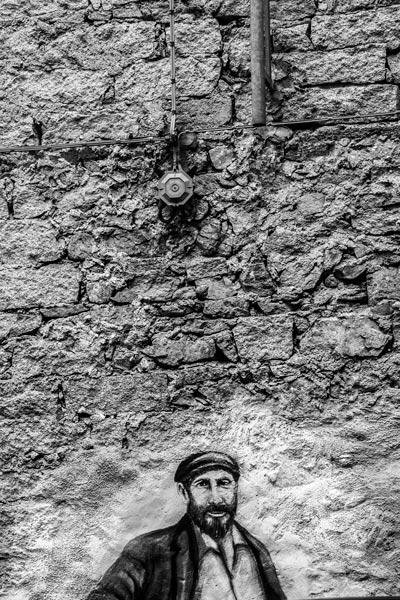Pintura mural de un señor en una pared de piedra. Orgosolo. Cerdeña
