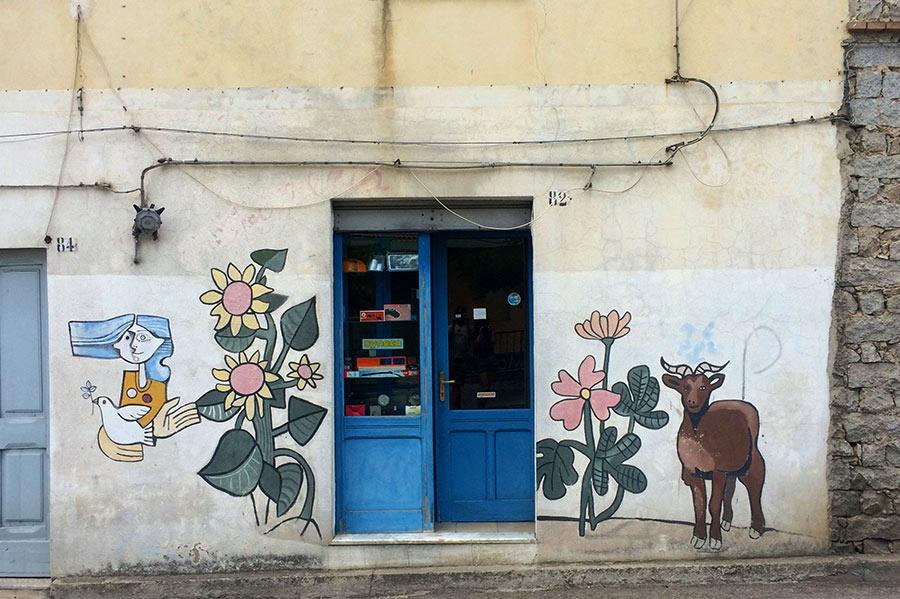 Pintura mural donde vemos flores, una cabra y una chica con formas picassianas con una paloma blanca. Orgosolo. cerdeña