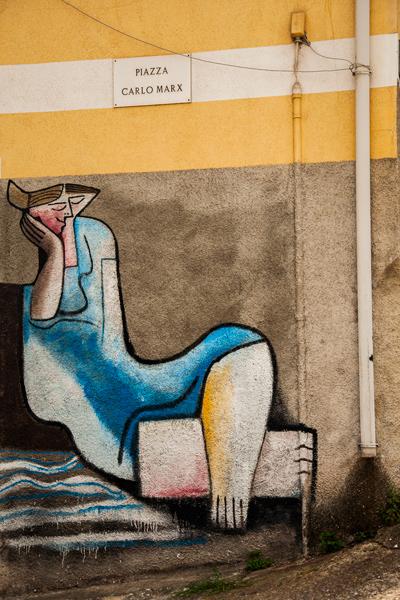 Pintura mural en la Plaza de Carlo Marx donde vemos a una mujer descansando sobre su brazo derecho. Orgosolo. Cerdeña.