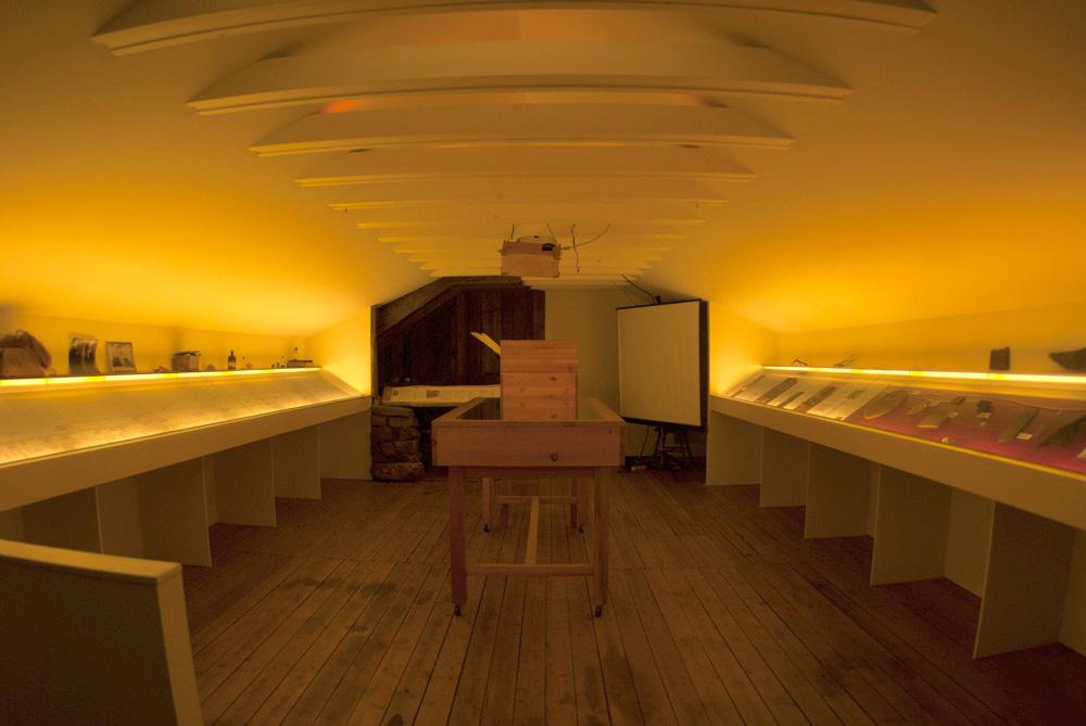 Parte superior de museo donde vemos las vitrinas llenas de runas y otros símbolos mágicos. Vista general.
