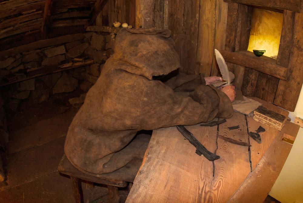 Monje escribiendo con una pluma en un casa típica de la época.