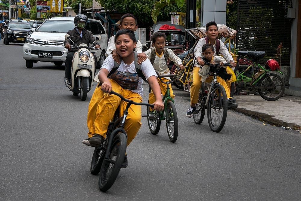 Niños sonrientes en bicicleta por el centro de la ciudad. Yogyakarta