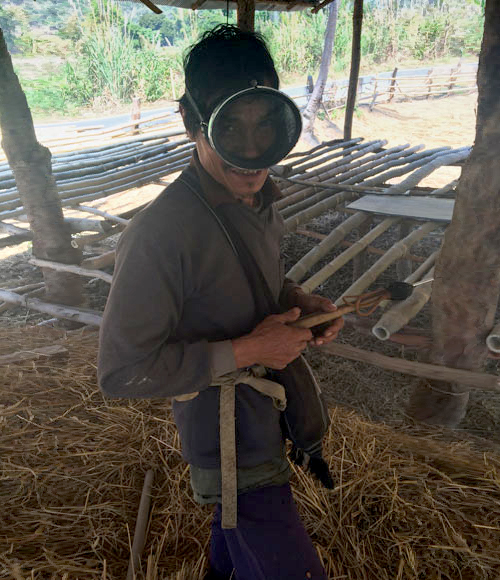Un pastor de búfalos se pone una gafas de buscar antiguas y posa con un fusil de pesca hecho a mano. Es de madera muy rudimentario.