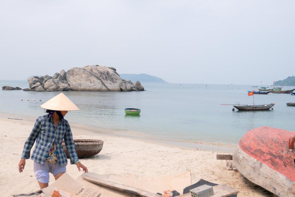 Pescadora con el típico gorro vietmita en una playita del pueblo rodeada de barcos y típicas barcas redondas vietnamitas. Islas Cham