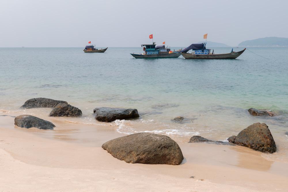 Una playa de arena blanca y al fondo el mar con barcos de pescadores vietnamitas. Islas Cham