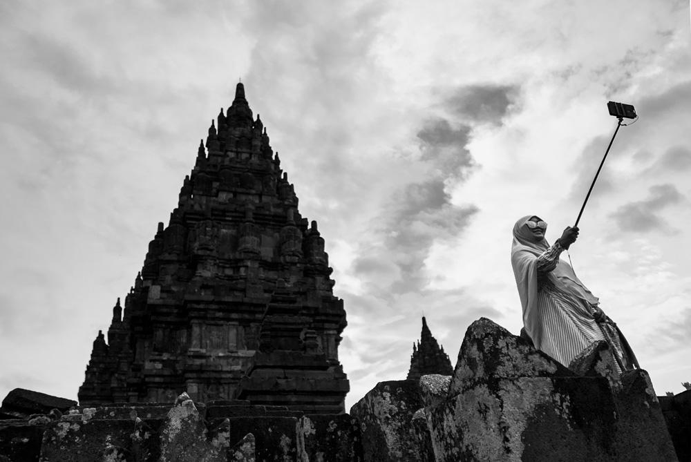 Señora con velo haciéndose un retrato con un palo de selfie en el templo de Prambanan. Yogyakarta