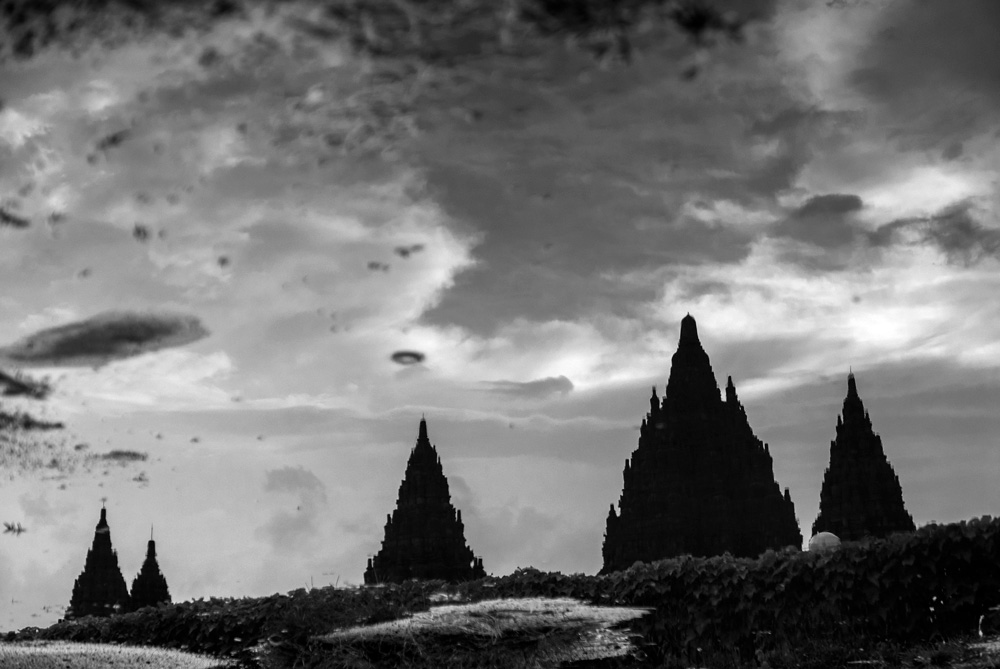 Reflejo de las torres de Prambanan en un charco. Fotografía en blanco y negro. Yogyakarta