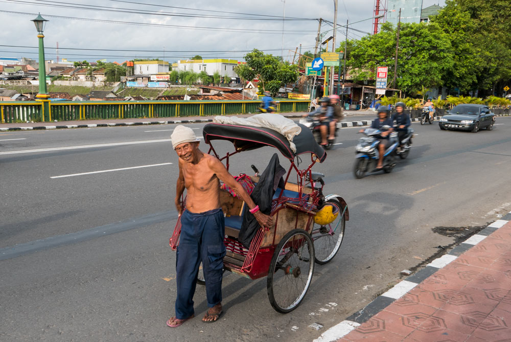 Señor mayor portando su tuc tuc con las manos en el puente de Gandolaya. Yogyakarta