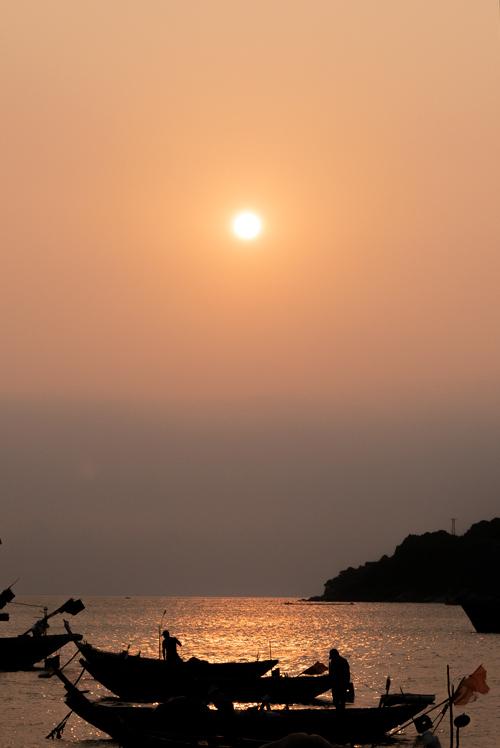 Barcos en plano más corto al atardecer. El cielo está teñido de un precioso color anaranjado. Islas Cham