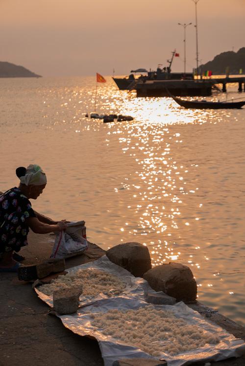 Precioso atardecer. Una mujer a contraluz seca arroz en el muelle, al fondo se ve el sol y barcos de pescadores. Islas Cham