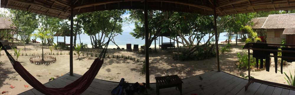 Desde la puerta de una cabaña observamos el mar. Una hamaca en el porche y unos arboles entre la cabaña y el mar nos protegen del sol. RAJA AMPAT. PAPÚA. INDONESIA