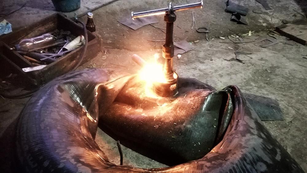 vulcanizando una rueda con fuego para parcharla.