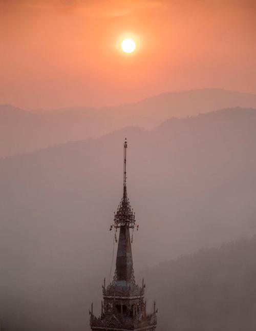 Especie de pináculo de los templos budistas con el sol poniéndose en su punta. espectacular atardecer. Mae Hong Son, la ciudad de la niebla.