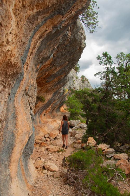 Chica caminando entre piedras. A su izquierda una pared enorme rocosa, a su derecha verdes árboles. Golfo de Orosei. Cerdeña