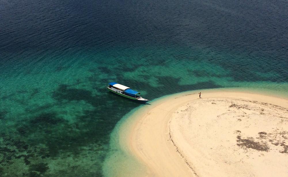 Playa vista desde lo alto de un montículo donde se aprecia su forma de lengua y lo transparente de sus aguas.  RUTA ISLA DE FLORES. INDONESIA. VIAJE EN MOTO 5 ETAPAS