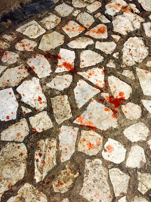 Suelo lleno de manchas de betel. Color rojo sangre.RUTA ISLA DE FLORES. INDONESIA. VIAJE EN MOTO 5 ETAPAS