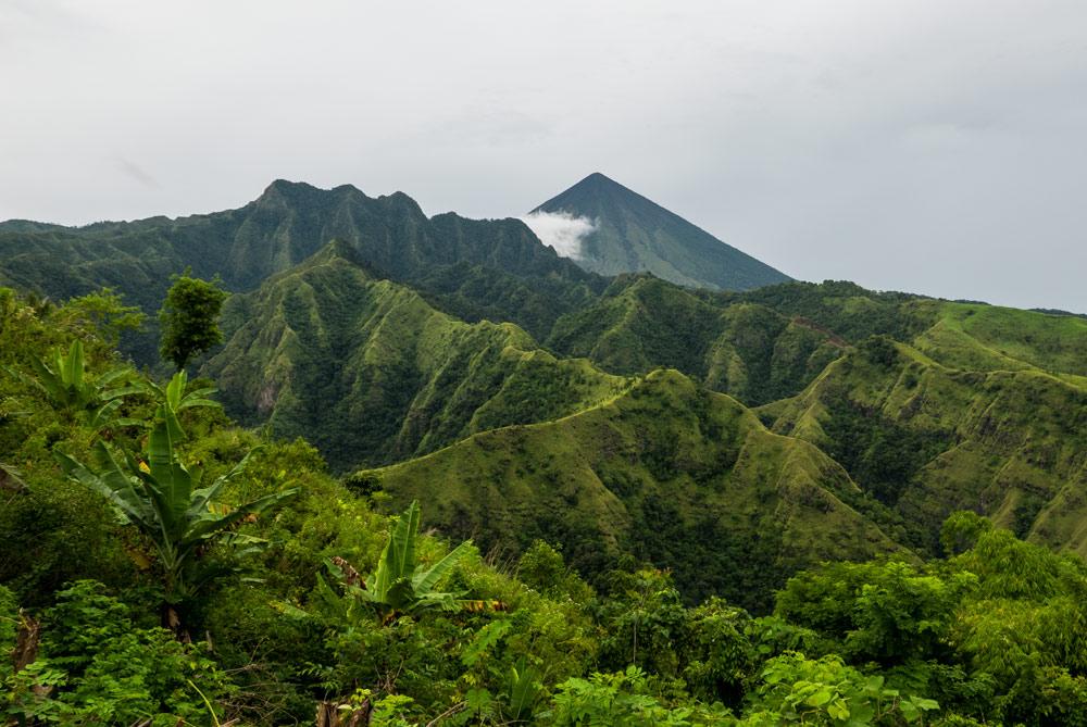 El volcán Iniere se ve al fondo de unsas coridlleras agrestes y empinadas de color verde intenso.. RUTA ISLA DE FLORES. INDONESIA. VIAJE EN MOTO 5 ETAPAS