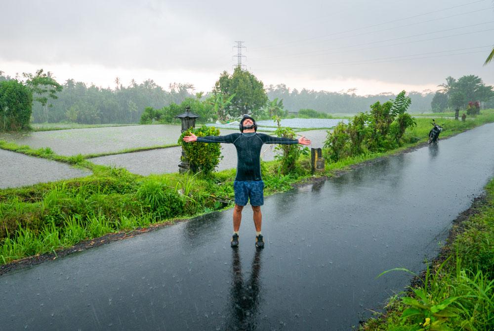 Chico disfruta de la lluvia abriendo sus brazos y dejando que el agua caiga sobre él. Los mejores seguros de viaje