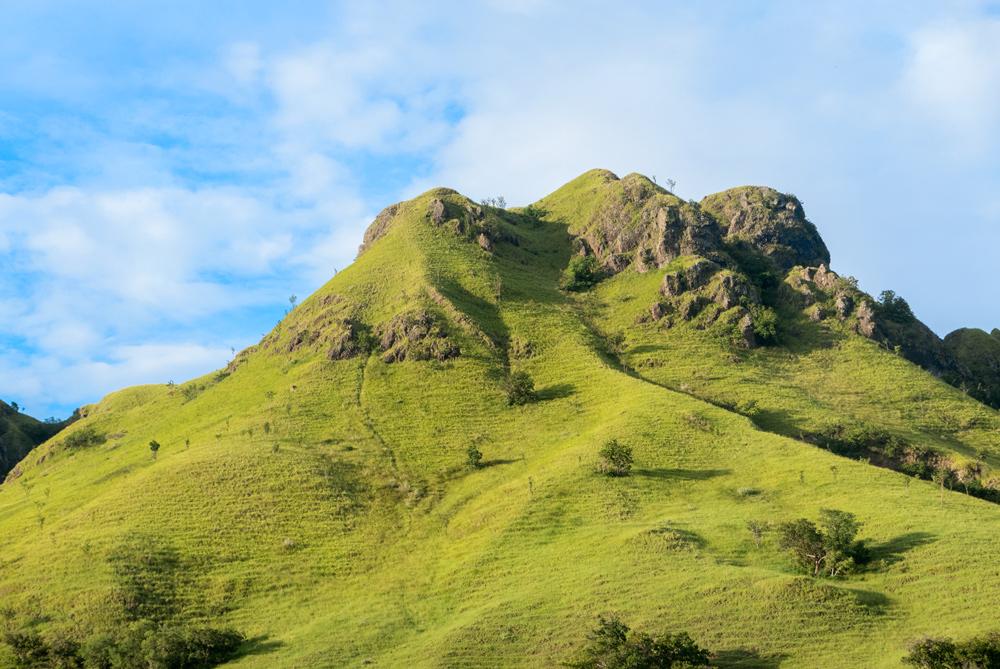 Montaña cubierta de hierva de un verde saturado. RUTA ISLA DE FLORES. INDONESIA. VIAJE EN MOTO 5 ETAPAS