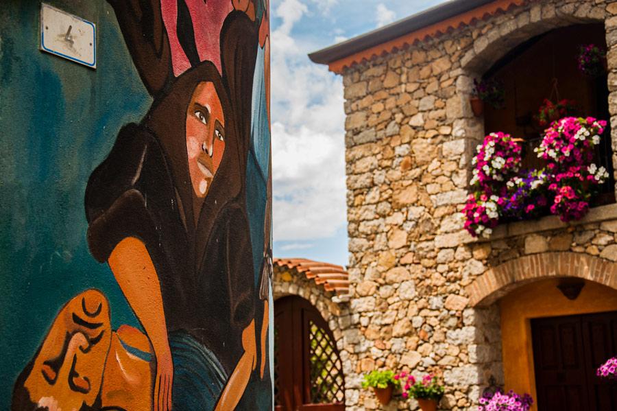 Preciosa foto con un mural con la cara triste de una chica y balcones de fondo repletos de flores. Orgosolo. Cerdeña