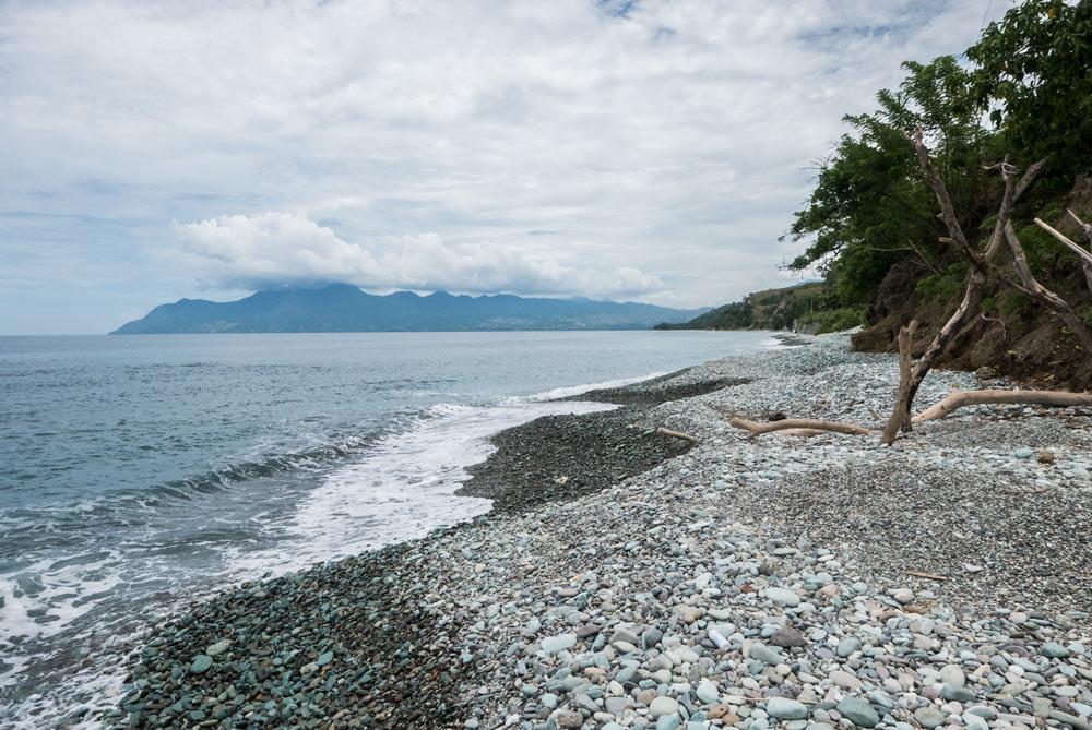 Playa de cantos rodados color azul/verde turquesa.RUTA ISLA DE FLORES. INDONESIA. VIAJE EN MOTO 5 ETAPAS