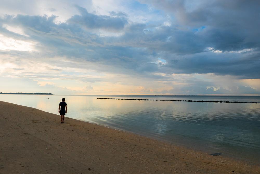 Chico pasea por una playa. El cielo se refleja en el mar haciendo un efecto espejo. Los mejores seguros de viaje