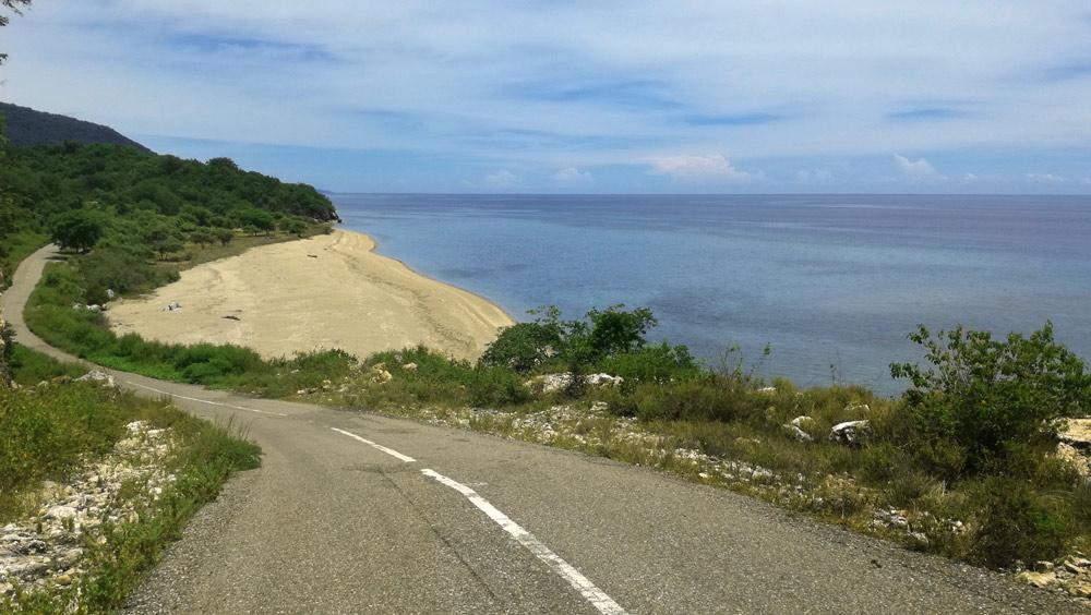 Una carretera discurre pegada a la playa en la zona norte de Flores..RUTA ISLA DE FLORES. INDONESIA. VIAJE EN MOTO 5 ETAPAS