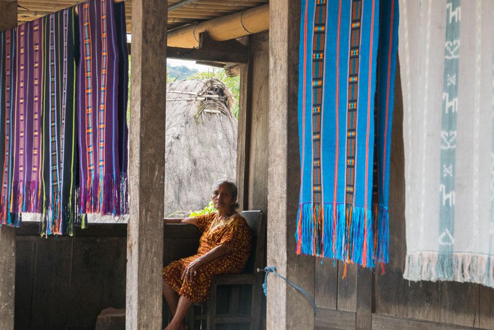 Señora en el porche de su casa mostrando sus Sarangs para la venta. RUTA ISLA DE FLORES. INDONESIA. VIAJE EN MOTO 5 ETAPAS