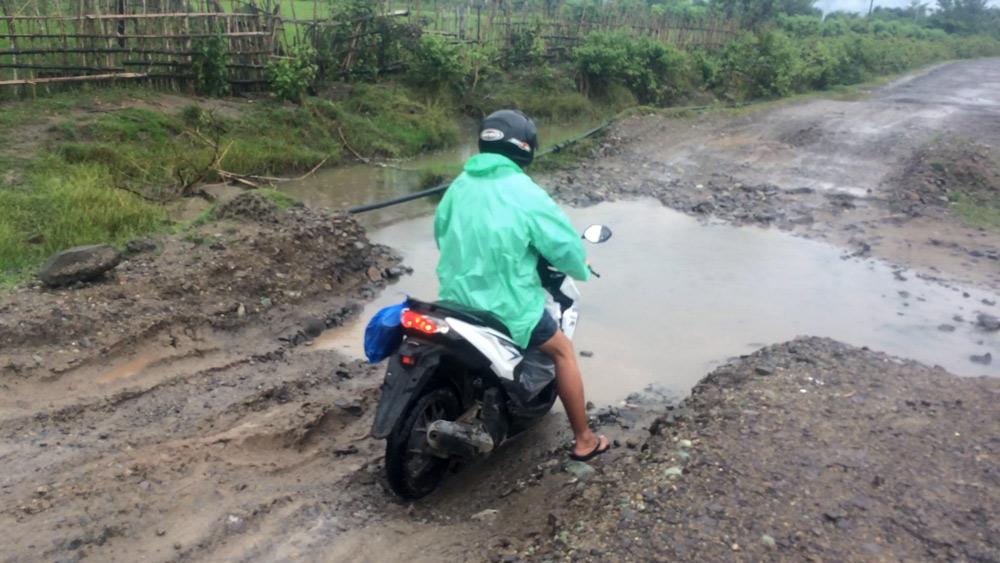 Socavones en la carretera de gran tamaño lleno de agua de la lluvia.RUTA ISLA DE FLORES. INDONESIA. VIAJE EN MOTO 5 ETAPAS