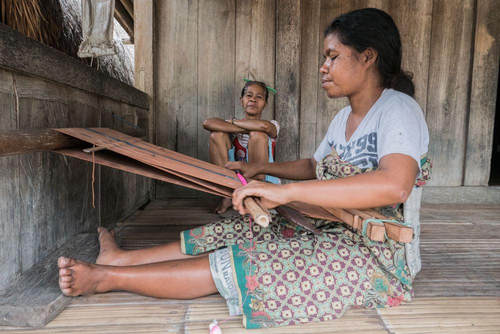 Una chica teje el típico Sarang en la entrada de su casa en Bena. RUTA ISLA DE FLORES. INDONESIA. VIAJE EN MOTO 5 ETAPAS
