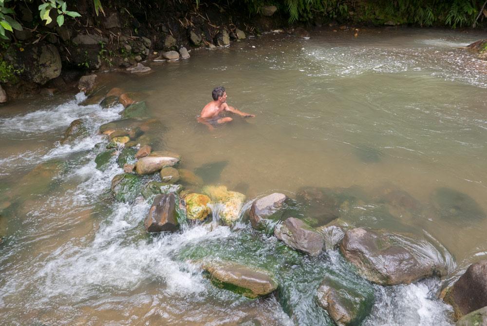 Un río de aguas calientes se mezcla con un arroyo de agua fría. RUTA ISLA DE FLORES. INDONESIA. VIAJE EN MOTO 5 ETAPAS