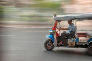 Un tuc-tuc (moto de tres ruedas para llevar a la gente) circulando por una calle. Excursiones en Bangkok.