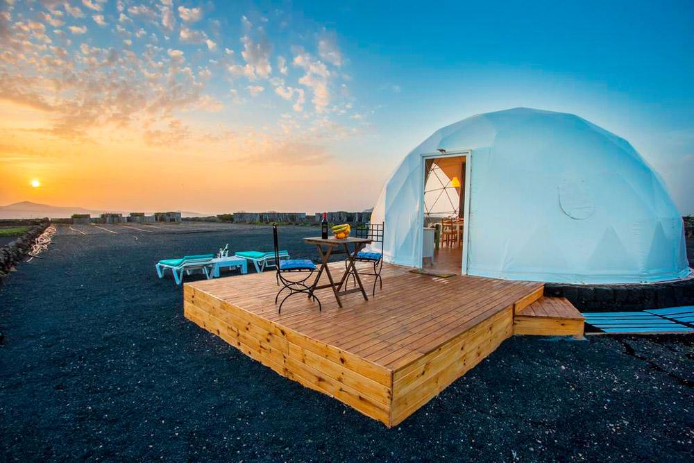 Tienda a modo de iglú en un paisaje volcánico al atardecer. 20 alojamientos originales en las Islas Canarias