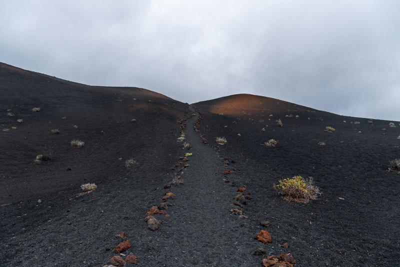 Sendero bajando por una colina de ceniza volcánica. Ruta de los Volcanes. Perder el Rumbo.