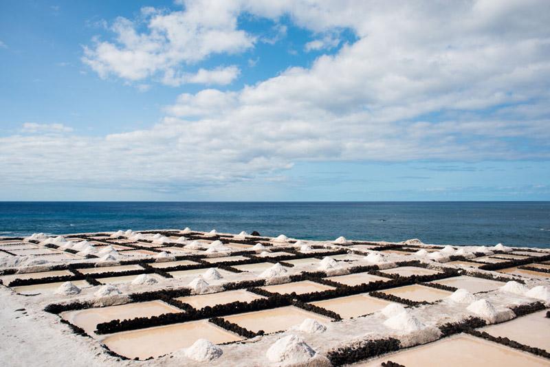 Salinas de Fuencaliente su disposición en damero y su color balnco contrastan con el negro y el azul de mar. Ruta de los Volcanes. Perder el Rumbo.