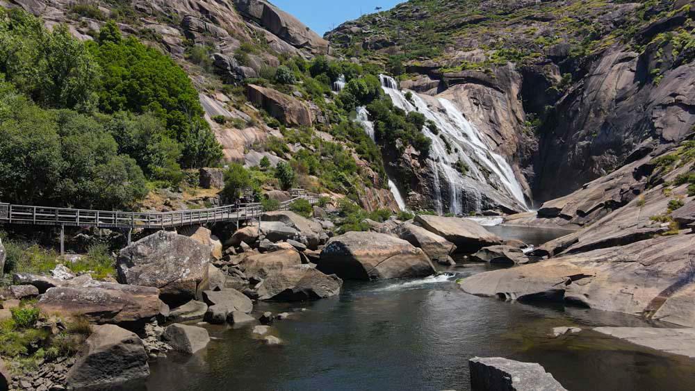 Vista general de la cascada y la pasarela de madera que lleva a ella. Cascada del Ézaro. Fervenza mágica en Galicia. Perder el Rumbo.o