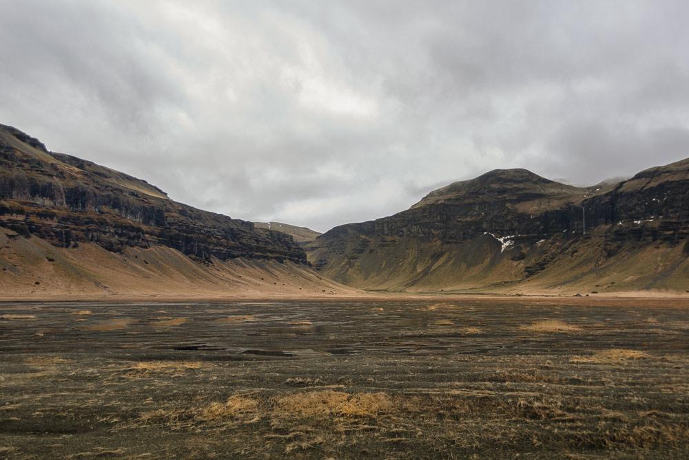 Una garganta entre dos montañas y una llanura con charcos hasta llegar a él. Curiosidades de islandia. Perder el Rumbo
