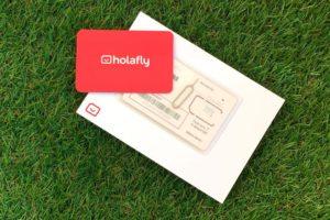 Fotografía de Holafly la tarjeta SIM prepago para viajar. Sobre un cesped verde. Perder el Rumbo