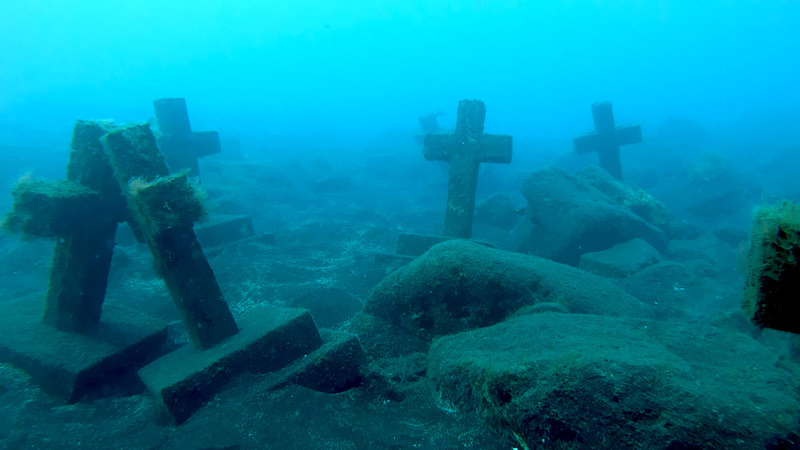 Debajo del mar se ven unas cruces en honor a unos mártires. La imagen es azul debido a lo profundo de las cruces.